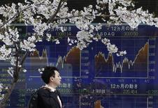 A man passes an electronic screen displaying graphs of the movements of share prices around the world as cherry blossoms are in full bloom in Tokyo April 9, 2012. REUTERS/Yuriko Nakao