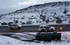 Firefighters and police officers stand near a pick-up truck that rolled on its side after the driver lost control along Interstate-17 in Yavapai County, Arizona, March 18, 2012. REUTERS/Joshua Lott