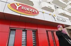 Женщина говорит по мобильному телефону у офиса компании Djezzy в Алжире 2 апреля 2012 года. Российская телекоммуникационная группа Вымпелком подала в четверг иск в арбитраж против правительства Алжира на фоне конфликта вокруг местного отделения Orascom Telecom, сообщила компания в четверг. REUTERS/Louafi Larbi