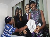 Colombian attorney Silvio Carrasquilla cleans a poster of U.S. President Barack Obama and his family which he hung on a wall inside his home in Turbaco, near Cartagena, April 11, 2012. Carrasquilla, Turbaco's former mayor who considers himself Colombia's number one Obama fan, is sprucing up his house by painting it the red, white and blue of the U.S. flag to celebrate Obama's arrival in Cartagena for the VI Summit of the Americas on Friday. REUTERS/Joaquin Sarmiento