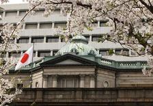 Цветущая вишня напротив здания Банка Японии в Токио, 10 апреля 2012 г. Один из регуляторов Банка Японии в марте безуспешно призывал к увеличению скупки гособлигаций, чтобы убедить рынки в том, что банк ориентируется на новый 1-процентный инфляционный ориентир, показал протокол заседания, опубликованный в пятницу. REUTERS/Yuriko Nakao