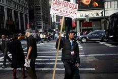 A man holds a sign advertising cash paid for gold and other precious metals in New York City, November 14, 2011. REUTERS/Mike Segar