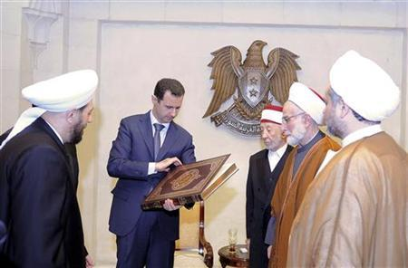 Syrian President Bashar al-Assad (2nd L) looks at a copy of the Koran he received from a delegation of religious leaders after talks with them in Damascus April 11, 2012. REUTERS/SANA/Handout