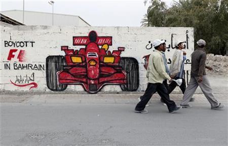 Men walk past anti-Formula One graffiti in the village of Barbar, west of Manama April 5, 2012. REUTERS/Hamad I Mohammed