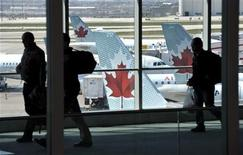 """Passengers walk past Air Canada planes on the runway at Pearson International Airport in Toronto April 13, 2012. Air Canada canceled at least 30 flights on Friday after what it called an """"illegal job action"""" by some of its pilots, the latest example of tense labor relations at the country's biggest airline. The carrier, in a heated dispute with two of its key unions, including the one representing its 3,000 pilots, said it was exploring its options to deal with the disruption, which came after pilots reportedly called in sick even though they were fit to fly. REUTERS/Mike Cassese"""