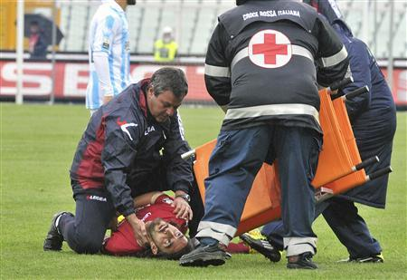 Livorno's Piermario Morosini is helped by doctors as he lies on the pitch during their Serie B soccer match against Pescara at the Adriatico stadium in Pescara April 14, 2012. Morosini has died after collapsing on the pitch with a cardiac arrest during an Italian second division game at Pescara on Saturday, prompting the soccer federation to postpone this weekend's professional games. REUTERS/Fabio Urbini