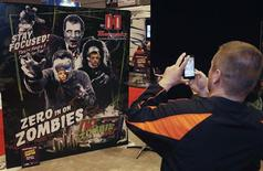 Two young attendees get their picture taken with a zombie poster during the National Rifle Association's (NRA) 141st Annual Meetings & Exhibits in St. Louis, in this April 13, 2012 file photo. The Hollywood-inspired zombie craze has extended to gun enthusiasts. REUTERS/Tom Gannam