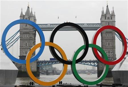 Olympic rings, mounted on a barge, are positioned in front of Tower Bridge on the River Thames in London February 28, 2012. REUTERS/Andrew Winning/Files