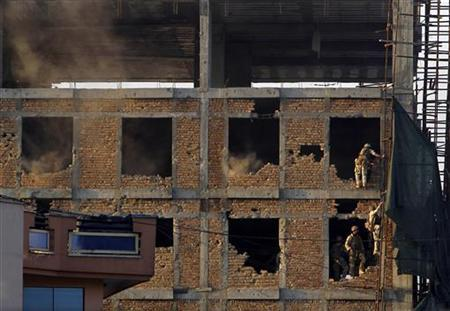 Afghan soldiers are seen at a construction site where an explosion took place during a battle between Afghan forces and Taliban insurgents including suicide bombers in Kabul April 16, 2012. REUTERS/Omar Sobhani