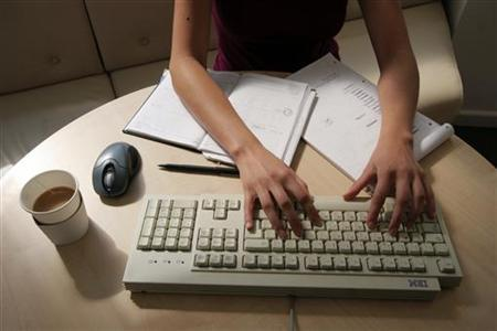 A generic picture of a woman working in an office sitting at her desk typing on a computer. REUTERS/Catherine Benson/Files