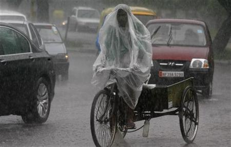 A man uses a plastic sheet to guard against a downpour while riding his trishaw in Chandigarh August 4, 2011. REUTERS/Ajay Verma/Files
