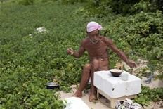 Seventy-six-year-old naked hermit Masafumi Nagasaki sits at table made from polystyrene box as he eats a food on Sotobanari island, off western coast of Iriomote island, Okinawa prefecture, April 14, 2012. REUTERS/Stringer