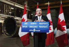 """A sign reading """"Jobs, Growth, and Prosperity"""" is seen as Natural Resources Minister Joe Oliver speaks at a news conference at the Automatic Coating Limited plant in Toronto, April 17, 2012. Despite the introduction of new rules to speed the approval of mines and pipelines in Canada, existing environmental reviews of major projects will carry on, Natural Resources Minister Joe Oliver told reporters on Tuesday. REUTERS/Mark Blinch"""