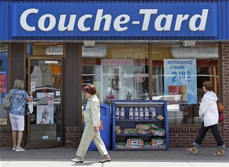 People walk past a Couche-Tard store in Quebec City June 9, 2010. REUTERS/Mathieu Belanger