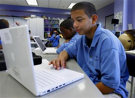 A student at the Lilla G. Frederick Pilot Middle School works on his laptop during a class in Dorchester, Massachusetts June 20, 2008. REUTERS/Adam Hunger/Files
