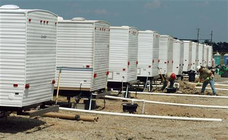 Workers hook up sewer and water to trailers provided by Federal Emergency Management Agency (FEMA) for workers at the Shell Sugarland facility in St. James, Louisiana, September 15, 2005. REUTERS/Allen Fredrickson