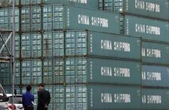 Men stand in a shipping container area in Tokyo April 19, 2012. REUTERS/Toru Hanai