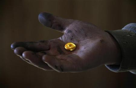 A small-scale miner holds his gold that was melted together at a processing plant located around 100km (62 miles) north of the Mongolian capital city Ulan Bator April 5, 2012. REUTERS/David Gray