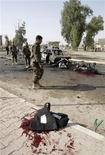 Сотрудники курдской службы безопасности работают на месте взрыва в Киркуке, 19 апреля 2012 года. По меньшей мере 36 человек погибли и больше 100 получили ранения в результате серии взрывов в Ираке в четверг, сообщили источники в полиции и больницах. REUTERS/Ako Rasheed