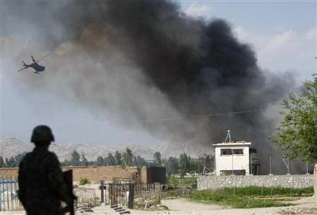 An Afghan National Army soldier keeps watch near the Provincial Reconstruction Team (PRT) as a NATO helicopter flies over the site of an attack in Jalalabad province April 15, 2012. REUTERS/Parwiz