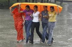 Girls cover themselves from rain in the northern Indian city of Chandigarh August 11, 2007. REUTERS/Ajay Verma
