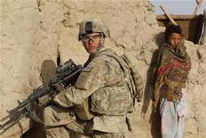 Афганская девочка стоит рядом с американским солдатом в провинции Кандагар 18 апреля 2012. Вашингтон принес извинения за опубликованные в среду снимки американских солдат на фоне изувеченных тел афганских повстанцев. Разгневанный увиденным Кабул потребовав ускорить вывод сил НАТО из Афганистана, а боевики- талибы пообещали мстить. REUTERS/Baz Ratner