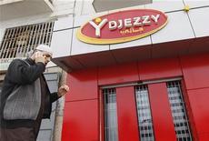 Мужчина говорит по телефону у офиса компании Djezzy в Алжире, 2 апреля 2012 г. Исполнительный директор алжирской Orascom Telecom Algerie (OTA), принадлежащей Вымпелкому и оказавшейся в центре спора с местными властями, взял отпуск по болезни, сообщила компания в четверг.  REUTERS/Louafi Larbi