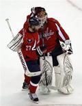 """Вратарь """"Вашингтона""""  Брэйден Холтби (справа) празднует с товарищем по команде Карлом Алзнером (слева) победу над """"Бостоном"""" на игре НХЛ в Вашингтоне, 20 апреля 2012 г. """"Вашингтон"""" смог обойтись в четверг без дисквалифицированного форварда Никласа Бэкстрема и обыграл прошлогоднего победителя Кубка Стэнли """"Бостон"""" со счетом 2-1, хотя совершил бросков вдвое меньше противника.  REUTERS/Kevin Lamarque"""