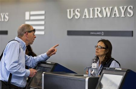 A US Airways passenger asks a question while checking in for his flight at Charlotte Douglas International Airport in Charlotte, North Carolina April 20, 2012. REUTERS/Chris Keane