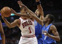 Chicago Bulls' Derrick Rose (1) looks to pass around Dallas Mavericks' Shawn Marion (0) and Rodrigue Beaubois (3) during the second period of their NBA basketball game in Chicago April 21, 2012. REUTERS/John Gress