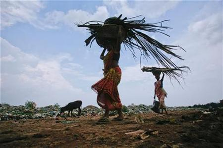 Women carry scraps from a dump yard against the backdrop of monsoon clouds, on the eve of World Environment Day, on the outskirts of Agartala, June 4, 2011. REUTERS/Jayanta Dey/Files