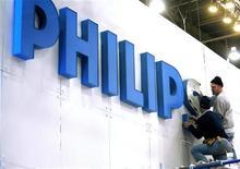 Рабочие укрепляют логотип Philips перед открытием специализированной выставки в Лас-Вегасе, 3 января 2008 года. Прибыль Philips Electronics в первом квартале 2012 года превысила ожидания инвесторов, укрепив надежды на начало долгожданного возвращения компании к активному росту. REUTERS/Las Vegas Sun/Steve Marcus