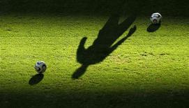 Тень футболиста на поле в Гамбурге, 18 июня 2006 года. Матчи еврокубков, чемпионатов Англии, Испании и Италии пройдут в Европе с понедельника по четверг. REUTERS/Suhaib Salem