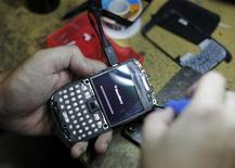 Homem conserta telefone Blackberry para cliente em uma loja em Jacarta. A Research in Motion, fabricante do BlackBerry, contratou o escritório de advocacia Milbank, Tweed, Hadley & McCloy para trabalhar em um plano de reestruturação que pode incluir venda de ativos, busca de joint-ventures ou licenciamento de patentes. 17/04/2012  RIM/ASIA REUTERS/Supri