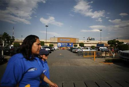 Employees walk outside a Wal-Mart store in Mexico City April 21, 2012. U.S. retail giant Wal-Mart Stores Inc squelched its own internal investigation of allegations made by a former executive of its subsidiary in Mexico that the Mexican division had orchestrated a campaign of bribery to grab market dominance, the New York Times reported on Saturday. REUTERS/Bernardo Montoya