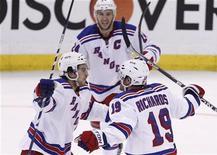 """Хоккеисты """"Нью-Йорк Рейнджерс"""" радуются шайбе, заброшенной в ворота """"Оттавы"""" в гостевой встрече, 23 апреля 2012 года. """"Нью-Йорк Рейнджерс"""" оказался в понедельник сильнее """"Оттавы"""" в шестом матче серии плей-офф Кубка Стэнли со счетом 3-2, и теперь победитель в противостоянии первой и восьмой команд Восточной конференции по итогам регулярного чемпионата НХЛ определится в решающем седьмом матче.  REUTERS/Chris Wattie"""