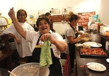 Head chef Malvin Nemeth, better known as Aunt Malvin, shows off her dance moves in a Budapest restaurant that serves food traditionally eaten by Hungary's Roma minority, April 21, 2012. REUTERS/Laszlo Balogh