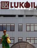 Женщина проходит около здания офиса компании Лукойл в Софии, 27 июля 2011 года. Крупнейшая в России частная нефтекомпания Лукойл на следующей неделе начнет эксплутационное бурение на иракском месторождении Западная Курна-2, где к концу 2013 года суточная добыча достигнет 150.000 баррелей нефти, сказал Рейтер глава компании Вагит Алекперов. REUTERS/Stoyan Nenov
