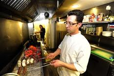 George Kapetanios poses for a photograph in the kitchen of Ta Dilina Greek restaurant in north London where he works as a chef, February 29, 2012. REUTERS/Paul Hackett