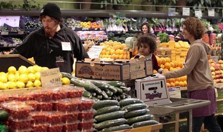 Whole Foods grocery store worker Adam Pacheco (L) stacks vegetables while customers shop in the produce section at the Whole Foods grocery story in Ann Arbor, Michigan, March 8, 2012. REUTERS/Rebecca Cook