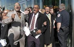 A group of Detroit pastors, including Homer Jamison (2nd R) and William Rideout (L), are escorted out of the Renaissance Center after disrupting General Electric Co's annual shareholders meeting being held in Detroit, Michigan April 25, 2012. REUTERS/Rebecca Cook