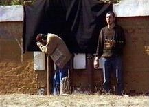 Двое чеченцев молятся 18 сентября 1997 года в Грозном перед публичной казнью по приговору шариатского суда, который признал их виновными в убийстве женщины и двух ее детей. МВД ищет признаки экстремизма в предложении чеченского адвоката легализовать в России суд шариата, идее, которую критики назвали иллюстрацией фиаско 12 лет политики Владимира Путина на Северном Кавказе и недоверия к судебной системе светского государства. REUTERS/Str Old