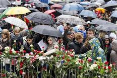 """People place flowers near the entrance of a courthouse where the trial of Norwegian anti-Muslim fanatic Anders Behring Breivik is conducted, as thousands turn up in poor weather at Youngstorget Square to sing a popular children's song in Oslo April 26, 2012. Around 40,000 people gathered in Oslo on Thursday to sing a song ridiculed by Breivik, who killed 77 people last July, as a show of protest against the right-wing activist's anti-immigrant views. Thousands more joined in song in towns across the country to sing """"Children of the Rainbow"""", a song that celebrates the sort of multiculturalism that Breivik said that motivated his killing spree. REUTERS/Heiko Junge/NTB Scanpix"""