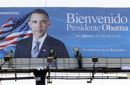 Men work in front of a billboard welcoming U.S. President Barack Obama, near the presidential house in San Salvador March 18, 2011. REUTERS/Luis Galdamez