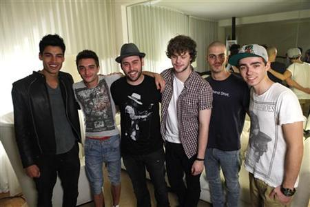 Manager Scooter Braun (3rd L) poses with members of British-Irish boyband The Wanted (from L-R) Siva Kaneswaran, Tom Parker, Jay McGuiness, Max George and Nathan Sykes for a portrait in Los Angeles, California April 4, 2012. Boy band fever is storming the music scene in the United States, led by the Brits who are breaking away from the slick, squeaky-clean image of old as they battle to become America's newest pin-ups. Picture taken April 4, 2012. REUTERS/Mario Anzuoni
