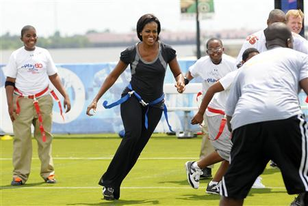 First lady Michelle Obama plays flag football with children and former NFL players and coaches during her ''Let's Move'' campaign to fight childhood obesity in New Orleans in this file photo taken September 8, 2010. REUTERS/Cheryl Gerber/Files