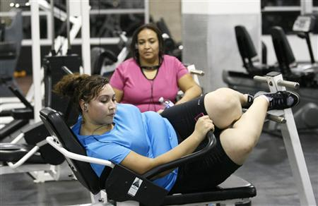 Jazmine Raygoza, 17, (L) does ab crunches during a workout at a gym as her mother Veronica (R) watches in Englewood, Colorado August 24, 2011. REUTERS/Rick Wilking