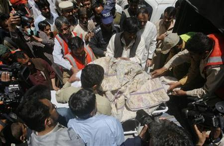 Members of the media gather as rescue workers and police shift the body of Khalil Rasjed Dale, a British doctor working with the International Committee of the Red Cross, at a hospital in Quetta April 29, 2012. REUTERS/Naseer Ahmed