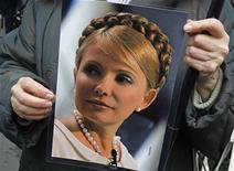 Uma partidária da líder de oposição e ex-primeira-ministra ucraniana, Yulia Tymoshenko, levanta um pôster durante um rali no exterior da casa presidencial em Kiev, 28 de março de 2012. A chanceler alemã, Angela Merkel, poderá cancelar a sua visita à Ucrânia durante a Eurocopa 2012, em junho, se a ex-primeira-ministra não for libertada da prisão até então. REUTERS/Gleb Garanich