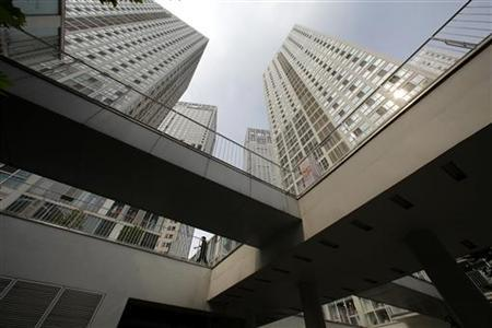A man walks amidst office buildings at the Jianwai Soho in Beijing's Central Business District August 20, 2010. REUTERS/Jason Lee